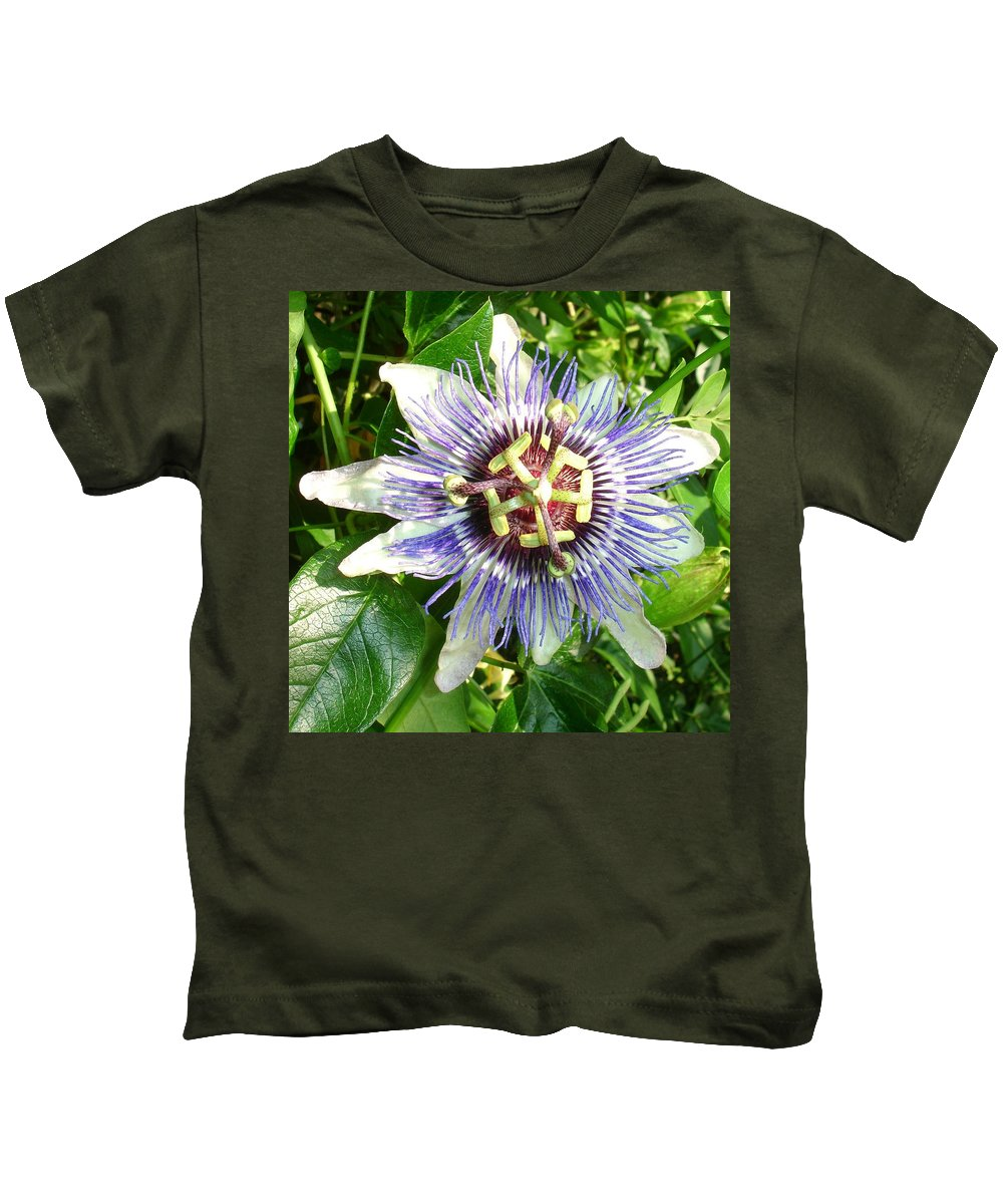 Flower Kids T-Shirt featuring the photograph Passiflora Against Green Foliage In A Garden by Taiche Acrylic Art