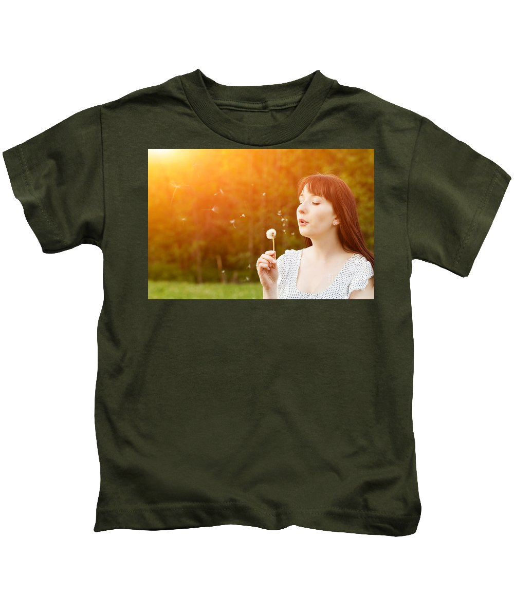 Woman Kids T-Shirt featuring the photograph Young Beautiful Woman Blowing A Dandelion In Spring Scenery by Michal Bednarek