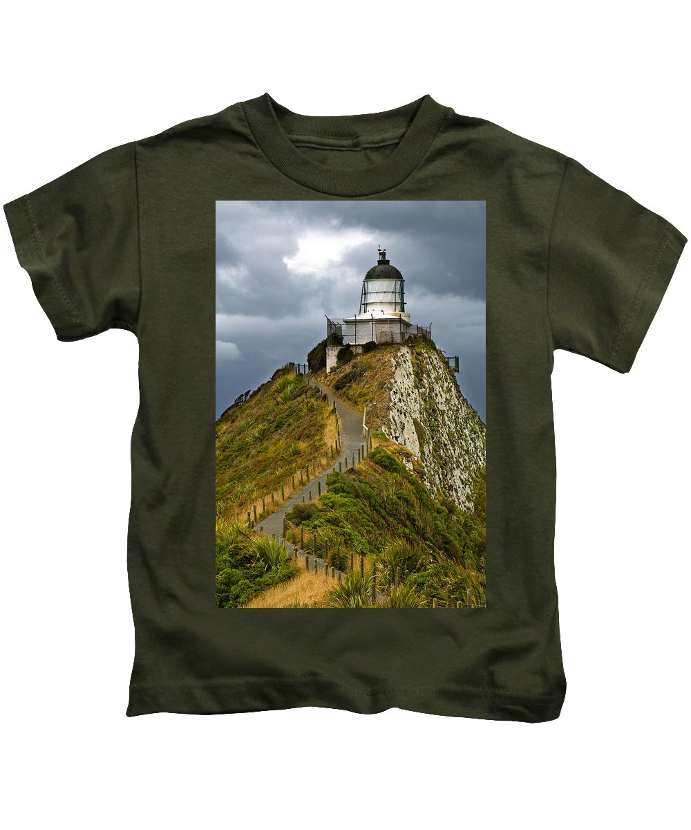Beach Kids T-Shirt featuring the photograph Nugget Point Light House And Dark Clouds In The Sky by U Schade