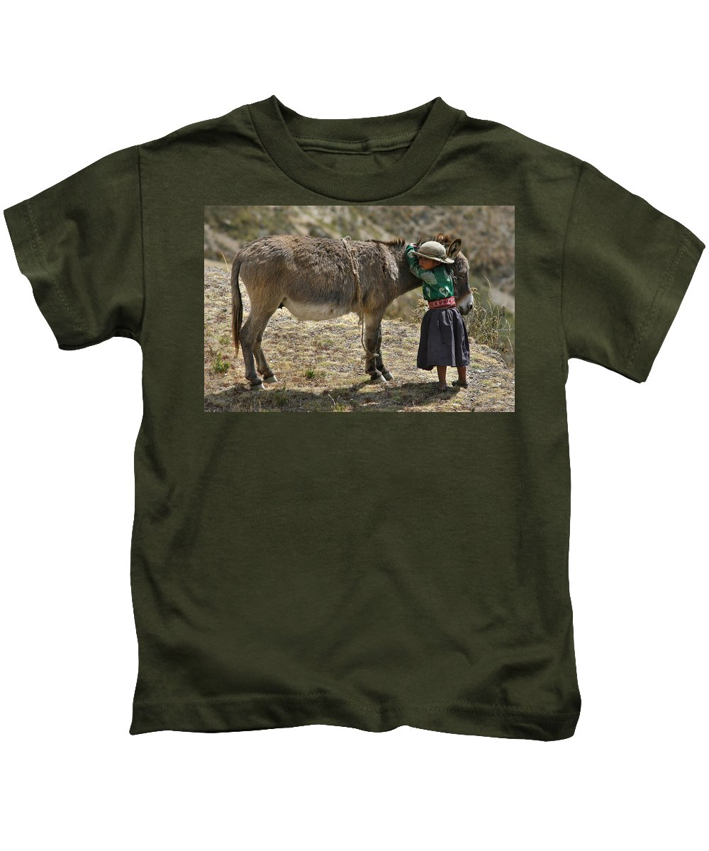 Girl Kids T-Shirt featuring the photograph Quechua Girl Hugging His Donkey. Republic Of Bolivia. by Eric Bauer