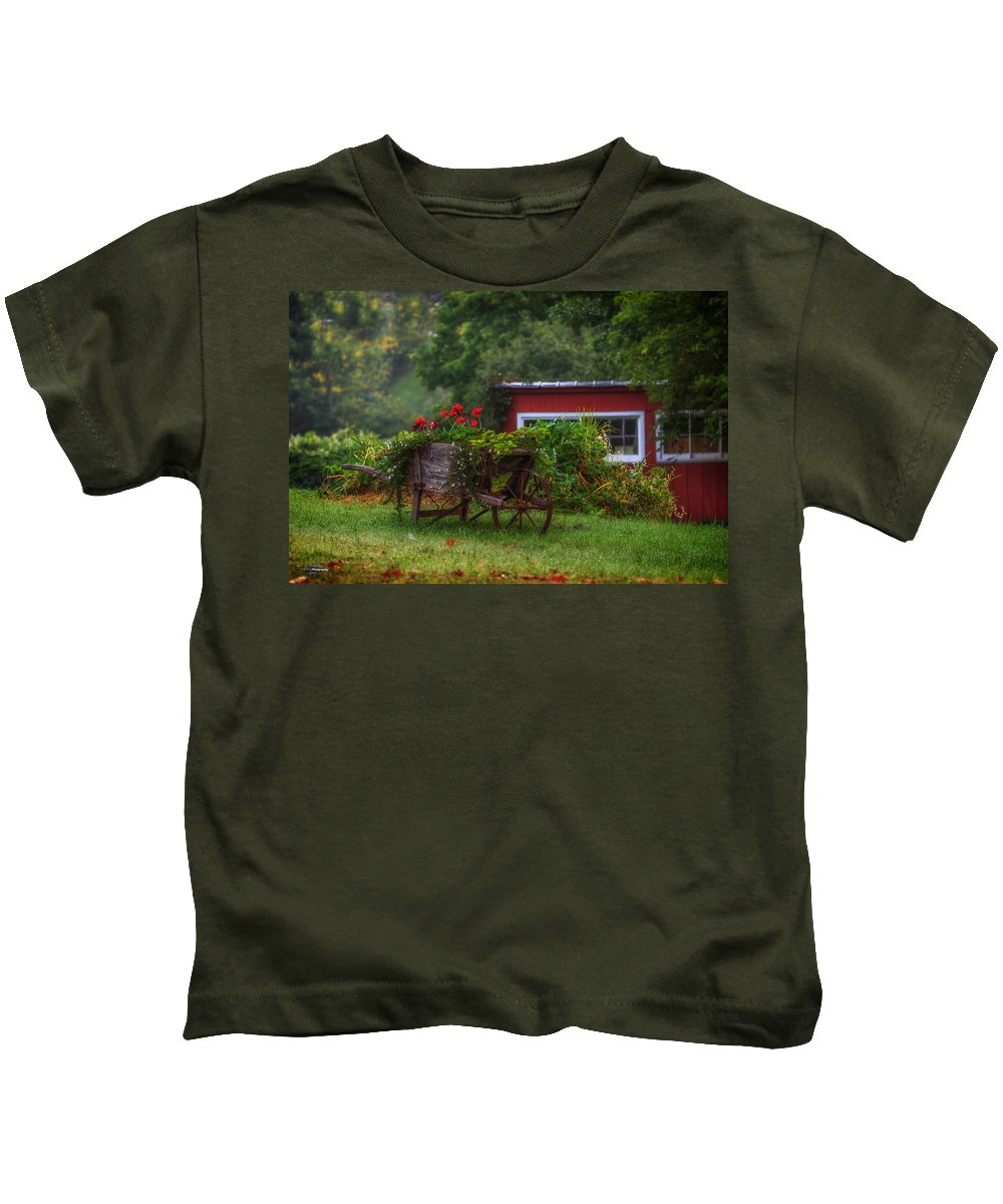Red Lowers Kids T-Shirt featuring the photograph The Old Wheelbarrel by Nancy Ann Roberts