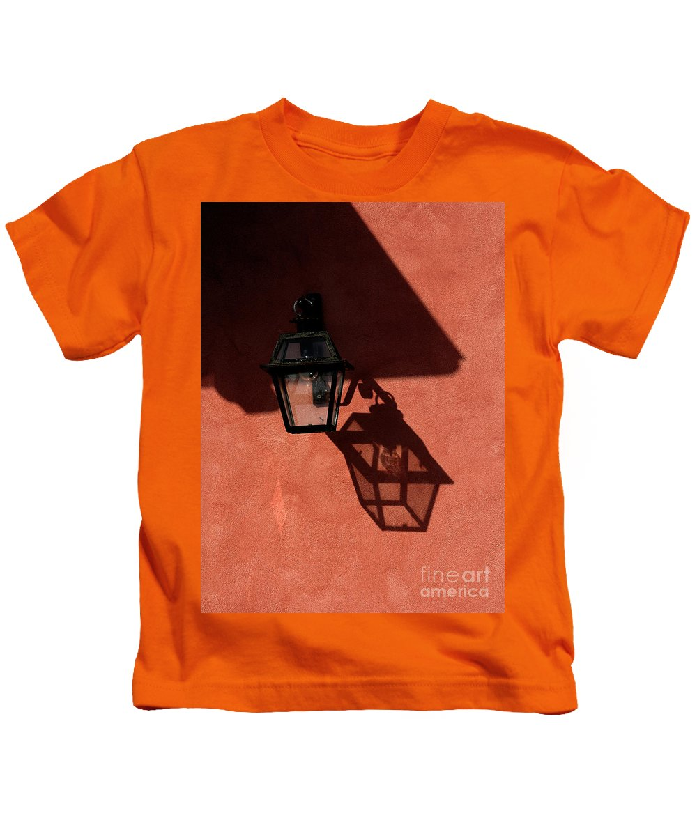 Lamp Kids T-Shirt featuring the photograph Lamp On Peach Wall by Mike Nellums