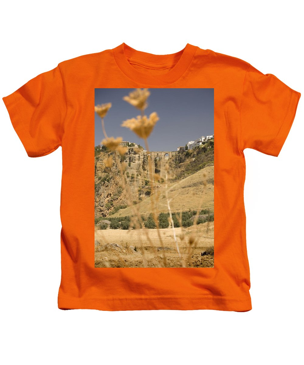 Tajo Kids T-Shirt featuring the photograph A View Of The Tajo De Ronda And Puente Nuevo Bridge Serrania De Ronda Andalucia Spain by Mal Bray