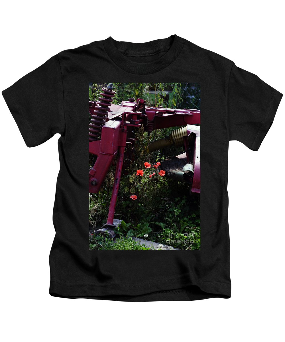Poppy Papaver Rhoeas Poppies England English Farm Farming Kids T-Shirt featuring the photograph Poppies Growing Amongst Farm Machinery In A Farmyard Near Pocklington Yorkshire Wolds East Yorkshire by Michael Walters