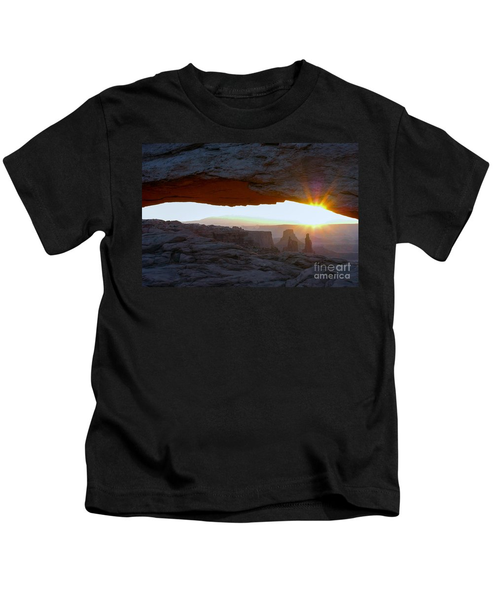 Mesa Arch Canyonlands National Park Utah Arches Sunrise Sunrises Red Rock Formation Formations Parks Reflected Light Early Morning Dawn Landscape Landscapes Landmark Landmarks Desertscape Desertscapes Kids T-Shirt featuring the photograph Starburst At Mesa Arch by Bob Phillips