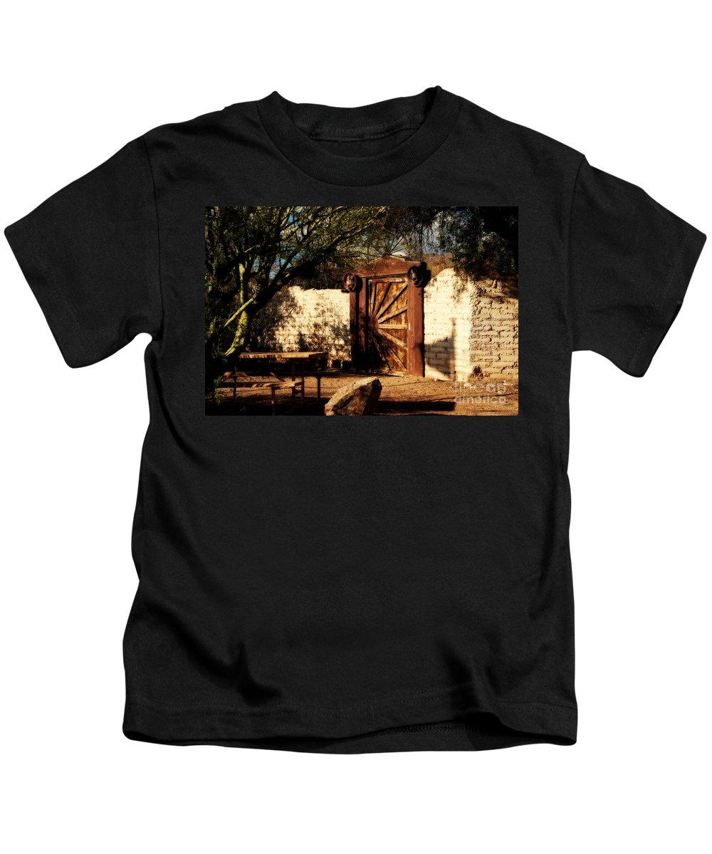Gate To Cowboy Heaven Kids T-Shirt featuring the photograph Gate to Cowboy Heaven in Old Tuscon AZ by Susanne Van Hulst