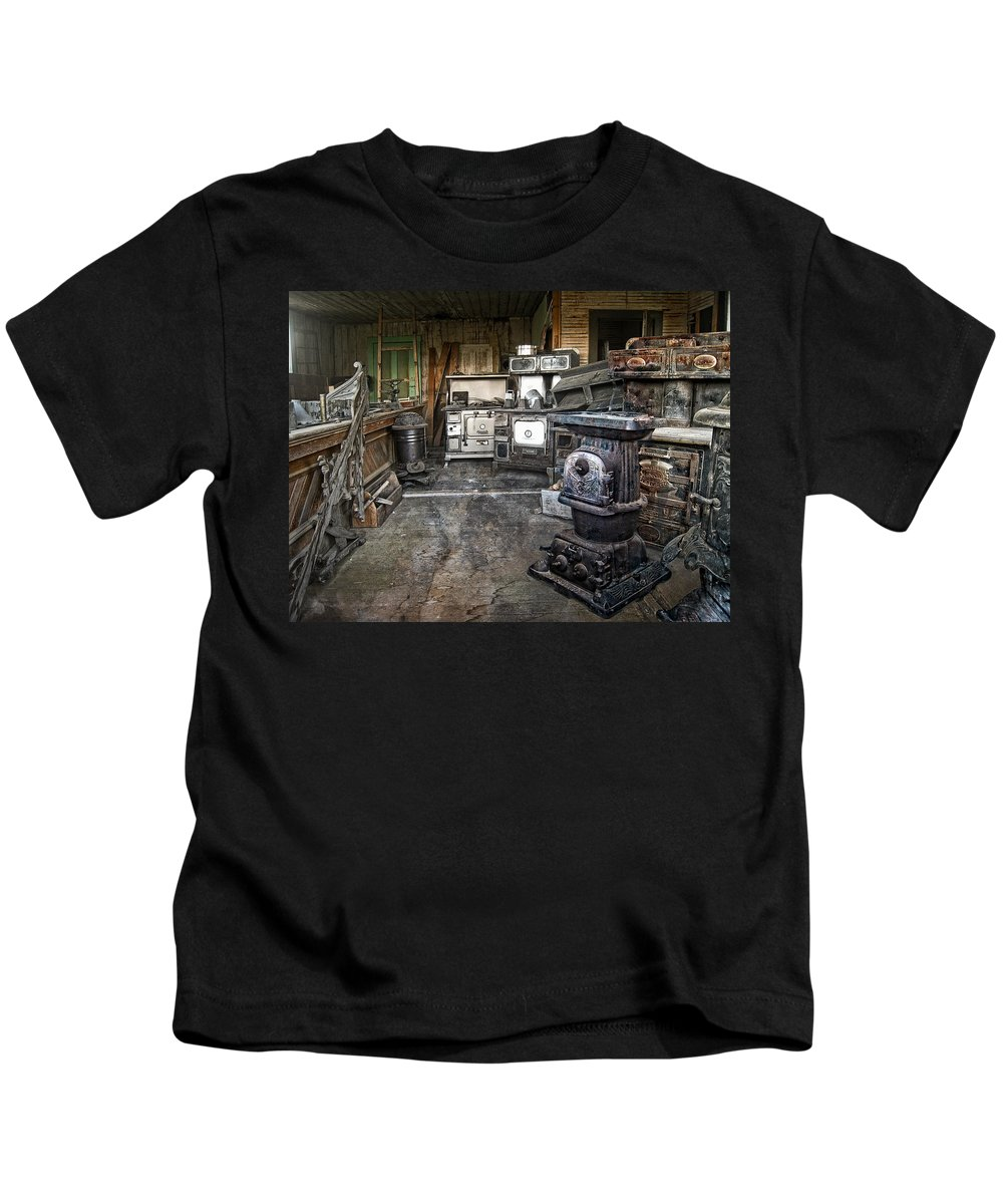 Stoves Kids T-Shirt featuring the photograph Ghost Town Stove Storage - Montana State by Daniel Hagerman