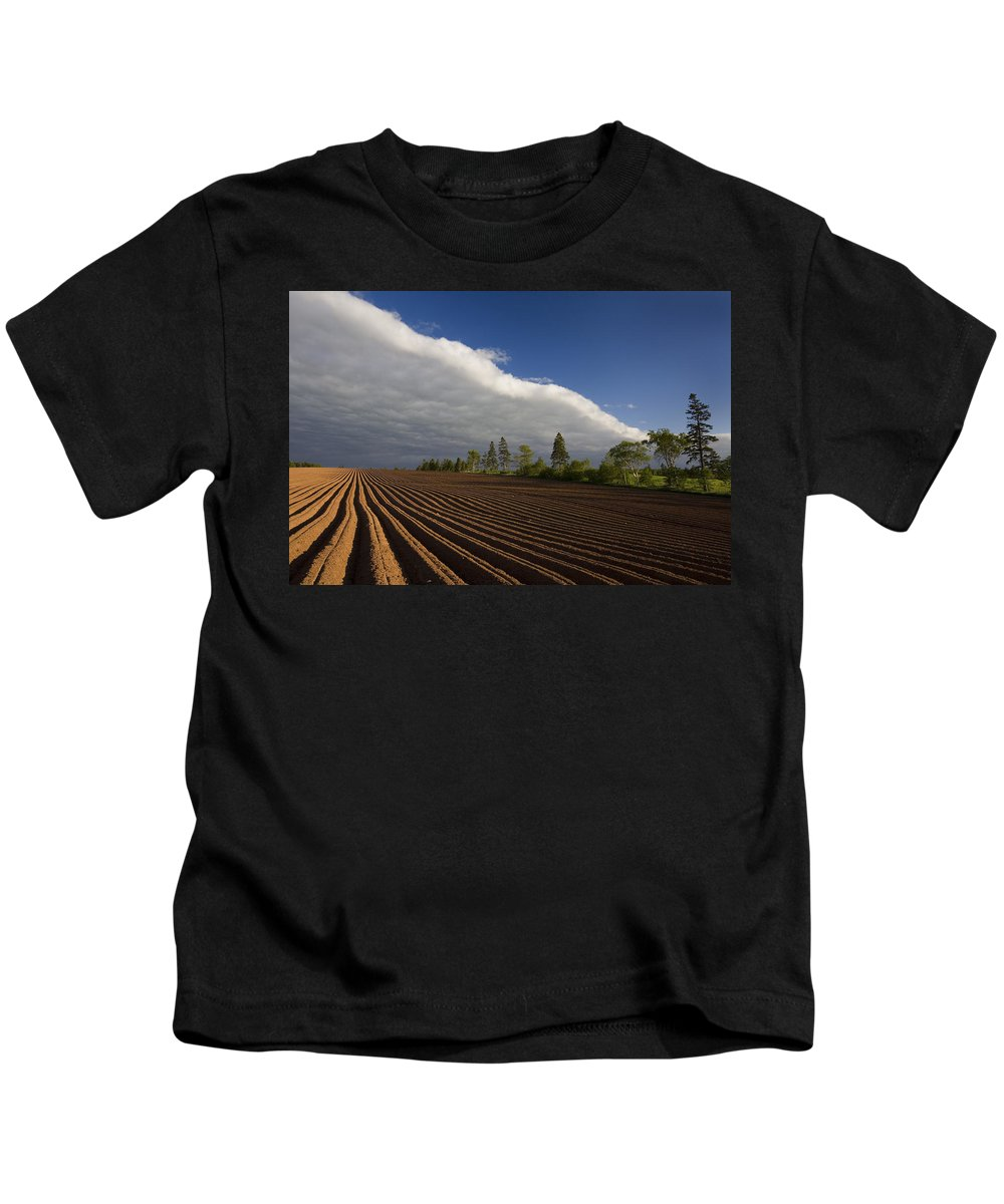 Agriculture Kids T-Shirt featuring the photograph Newly Planted Potato Field And Clouds by John Sylvester