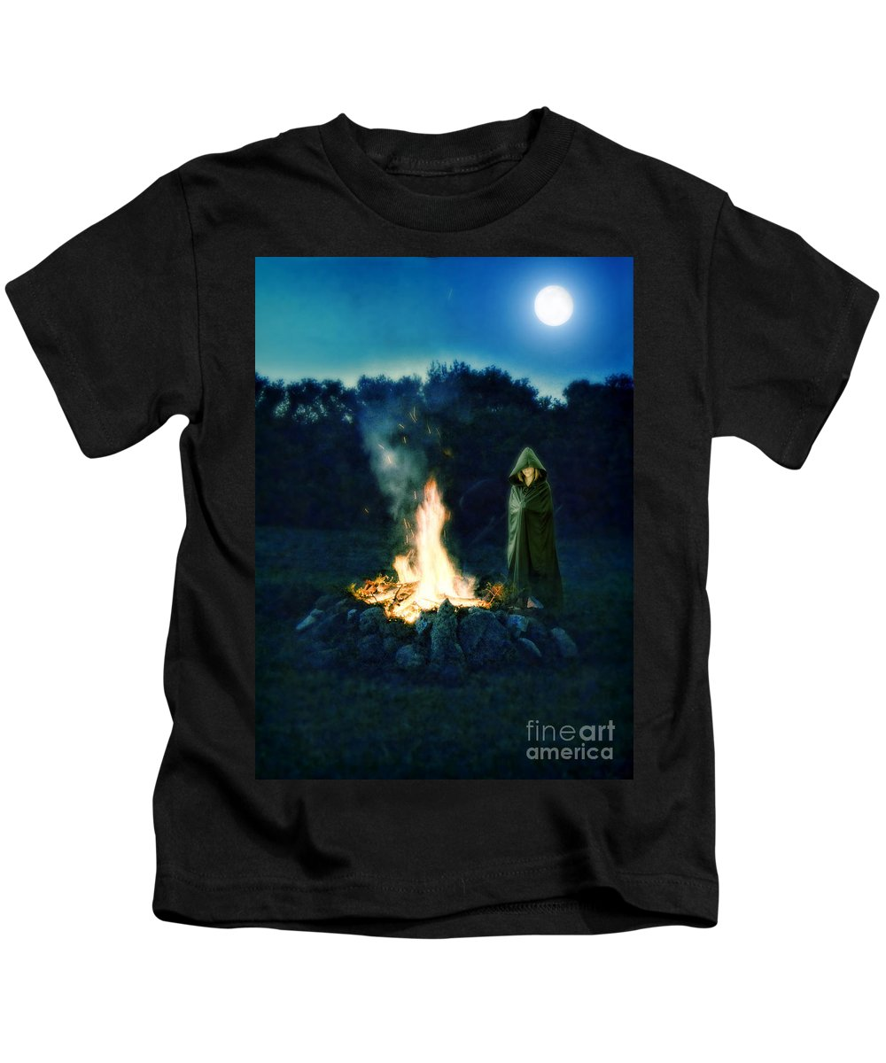 Fire Kids T-Shirt featuring the photograph Person Standing By A Bonfire In The Moonlight by Jill Battaglia
