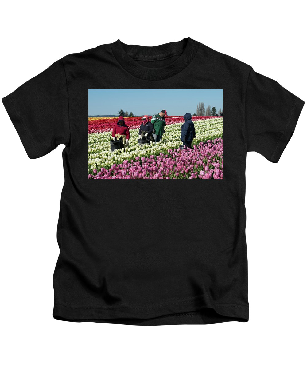Agricultural Workers Kids T-Shirt featuring the photograph Farm Workers In Tulips by Tom Cochran
