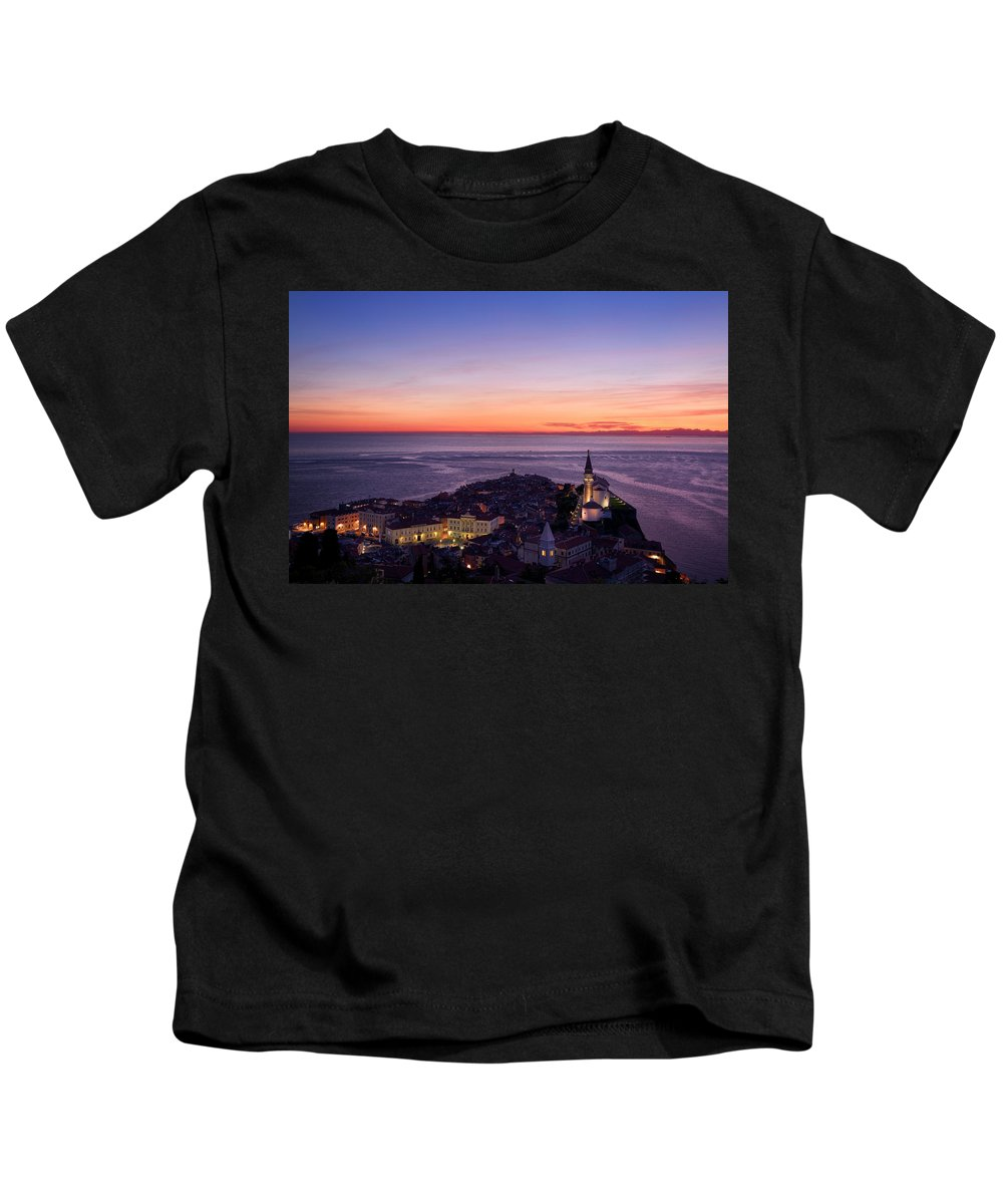 Piran Kids T-Shirt featuring the photograph Purple Light On The Adriatic Sea After Sundown With Lights On Pi by Reimar Gaertner