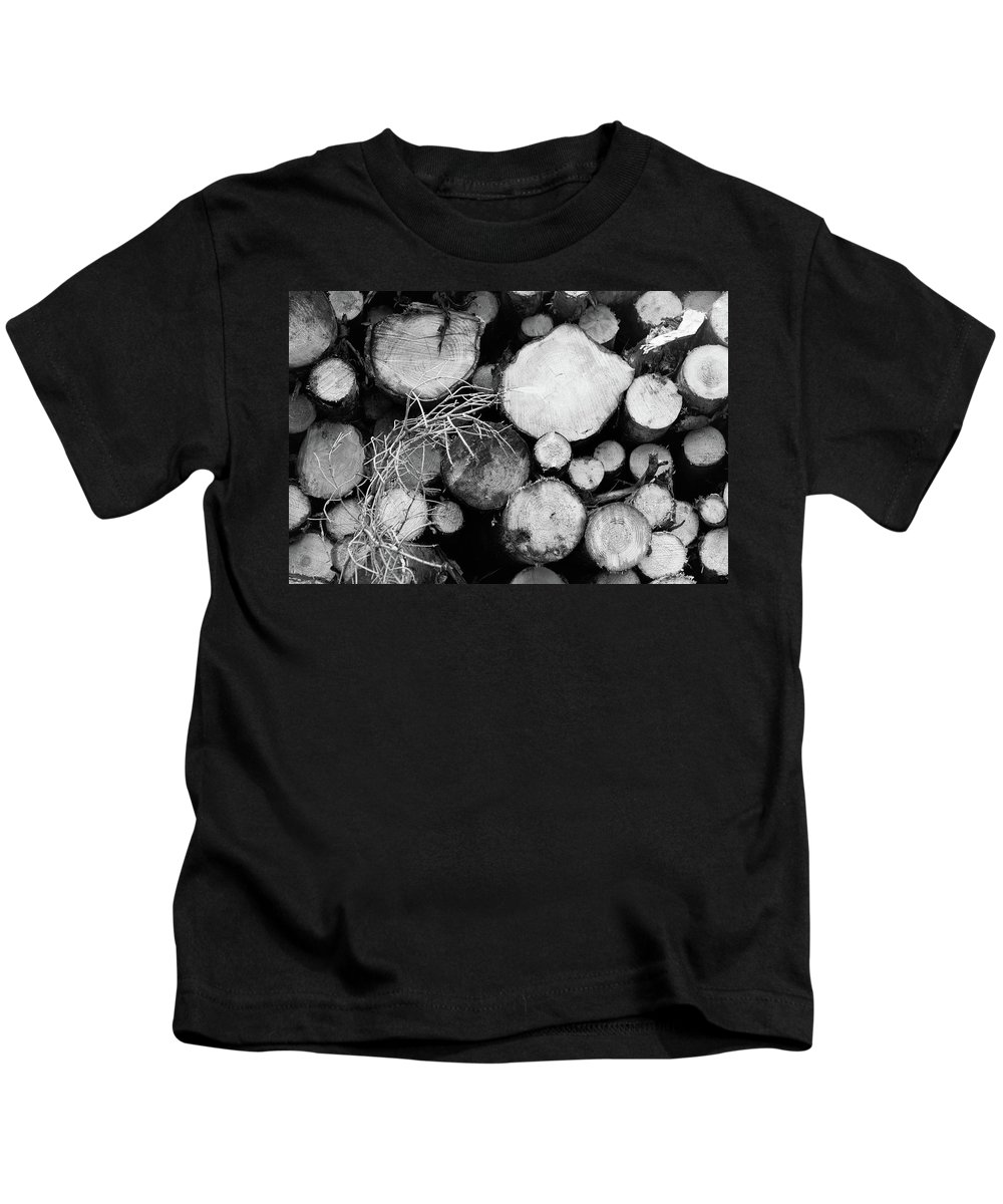 Cumbria Lake District Kids T-Shirt featuring the photograph Stacked Wood Logs In Black And White by Iordanis Pallikaras