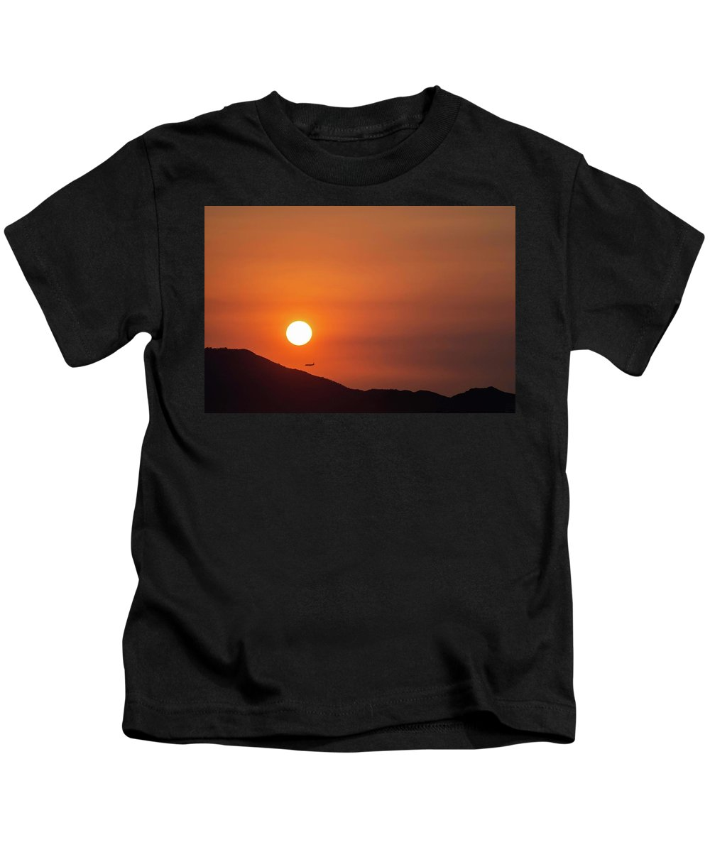 Sunset Kids T-Shirt featuring the photograph Red sunset and plane in flight by Hannes Roeckel