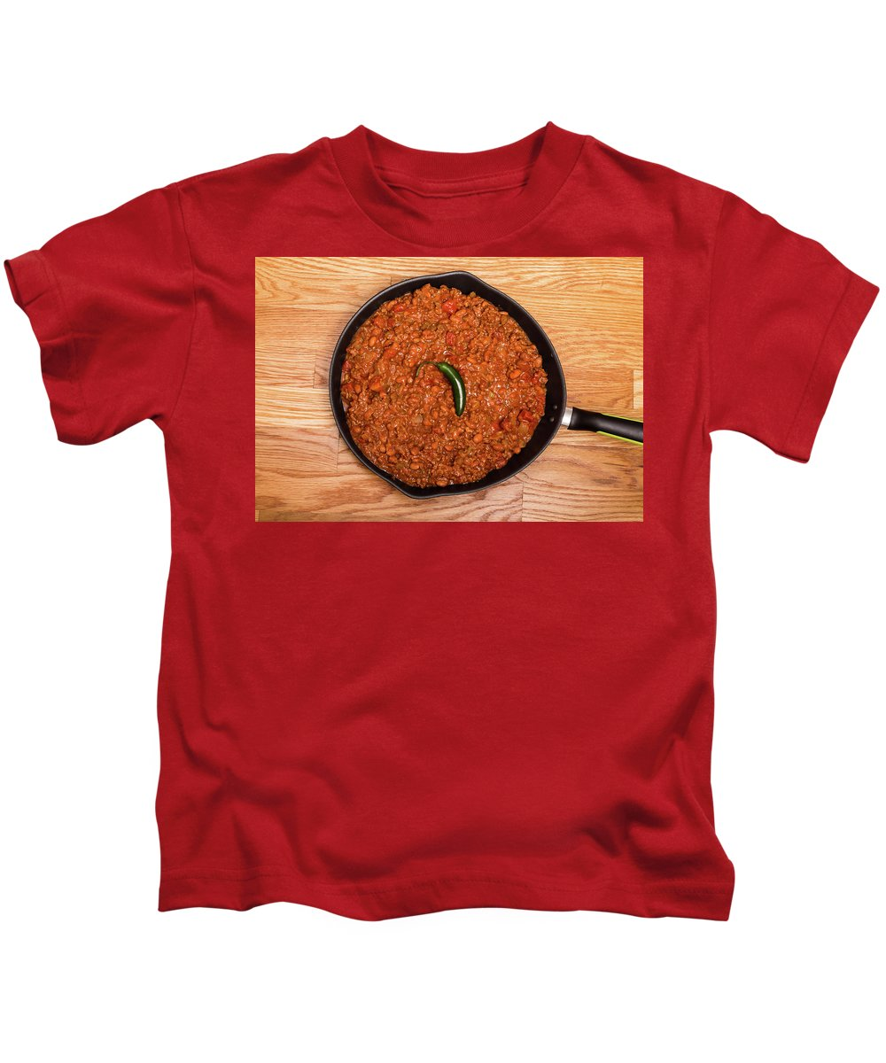 Beans Kids T-Shirt featuring the photograph Chili In Black Pan On Wood Table With Jalapeno Pepper by Darryl Brooks