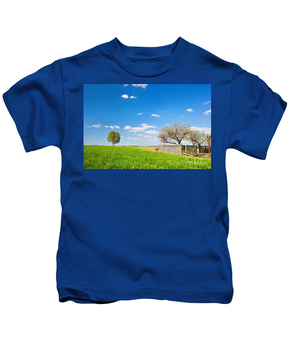 Field Kids T-Shirt featuring the photograph Countryside Landscape During Spring With Solitary Trees And Fence by Michal Bednarek