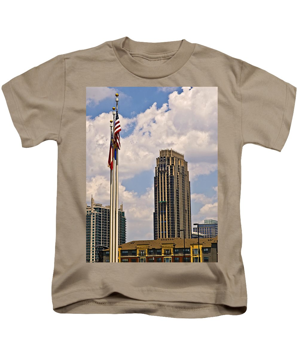 America Kids T-Shirt featuring the photograph Buildings And Flags Against Sky by Susan Leggett