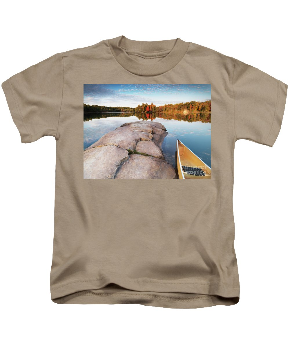 Canoe Kids T-Shirt featuring the photograph Canoe At A Rocky Shore Autumn Nature Scenery by Oleksiy Maksymenko