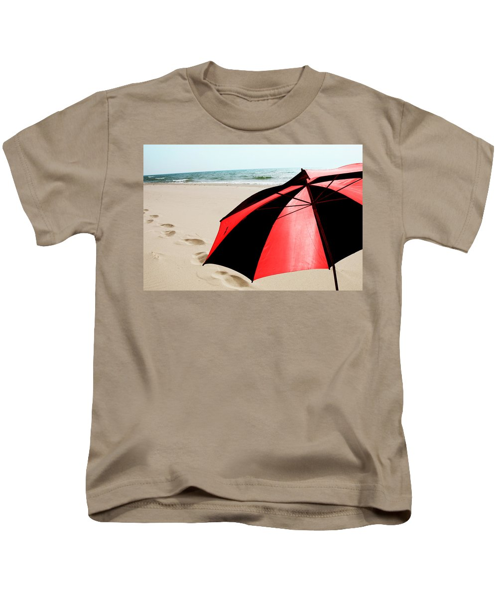 Art Kids T-Shirt featuring the photograph Red And Black Umbrella On The Beach With Footprints by Randall Nyhof