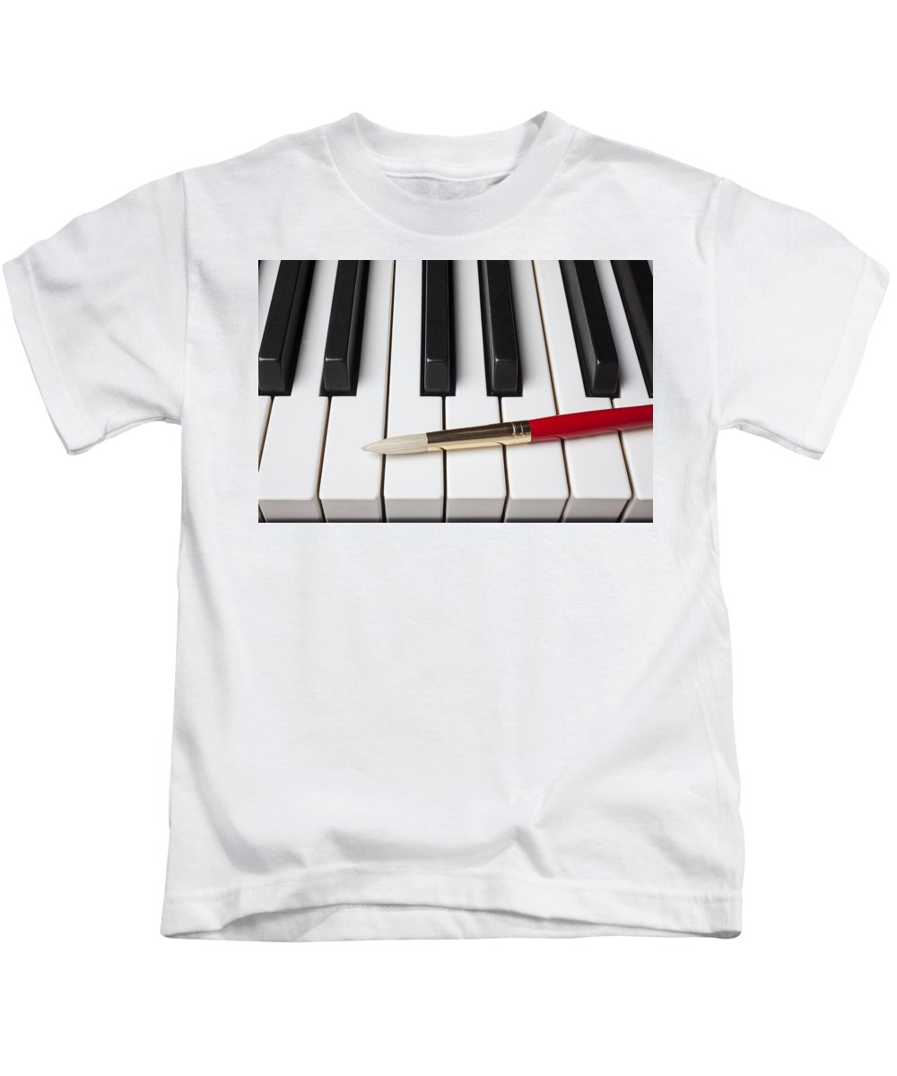 Artist Kids T-Shirt featuring the photograph Artist Brush On Piano Keys by Garry Gay