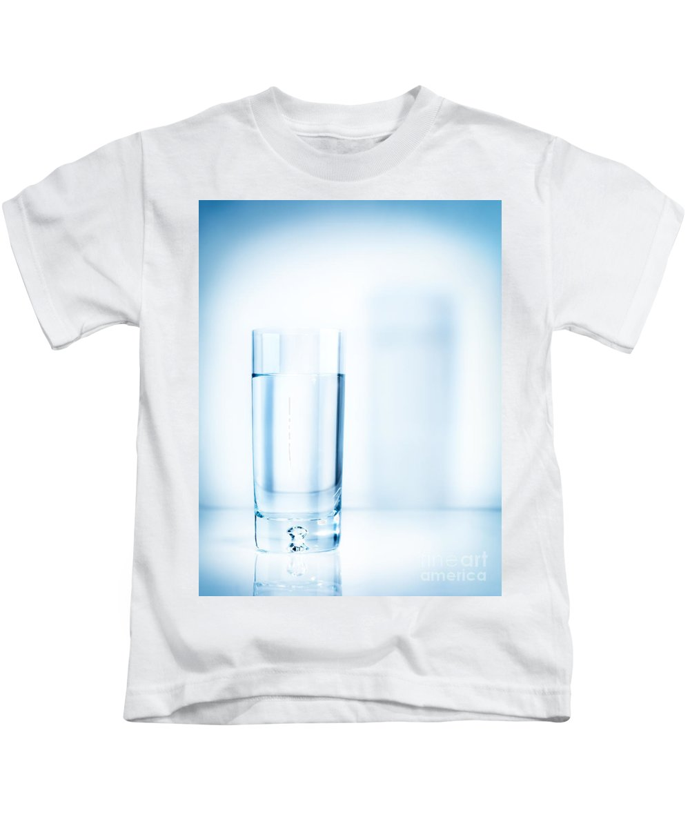 Water Kids T-Shirt featuring the photograph Glass Of Water On Light Blue Background by Maxim Images Prints