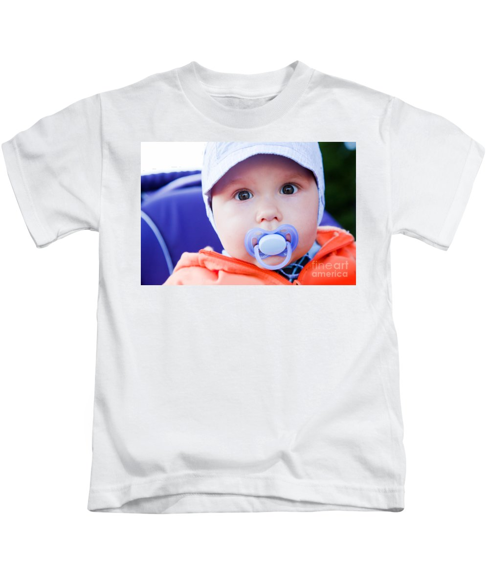 Child Kids T-Shirt featuring the photograph Young Baby Boy With A Dummy In His Mouth Outdoors by Michal Bednarek