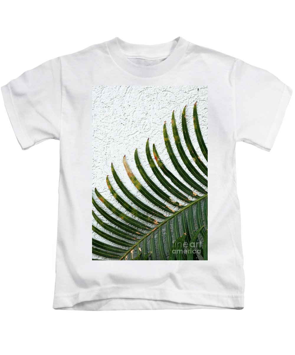 Blades Kids T-Shirt featuring the photograph Bladed Leaf Against Stucco Wall by Mike Nellums