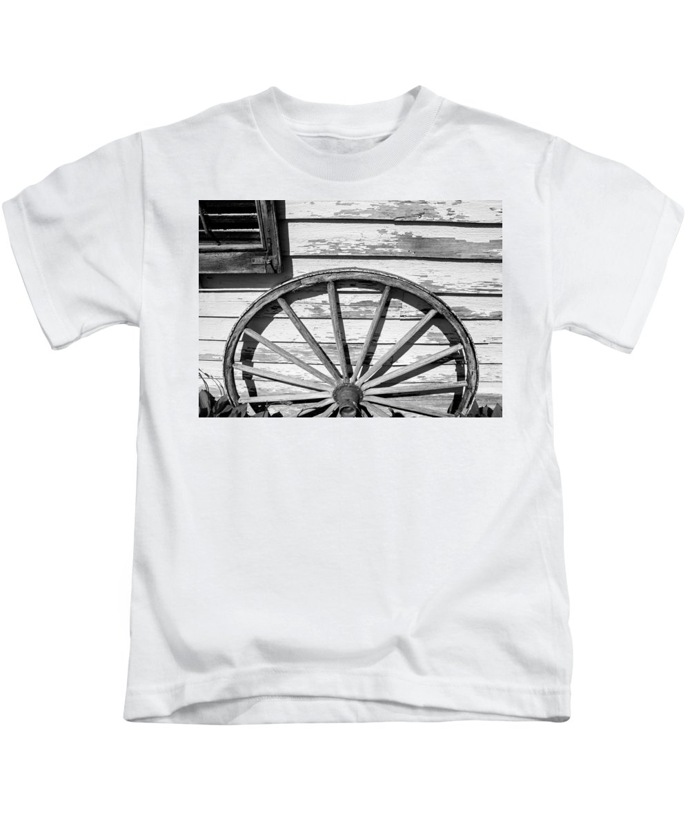 Wagon Kids T-Shirt featuring the photograph Antique Wagon Wheel In Black And White by Photographic Arts And Design Studio