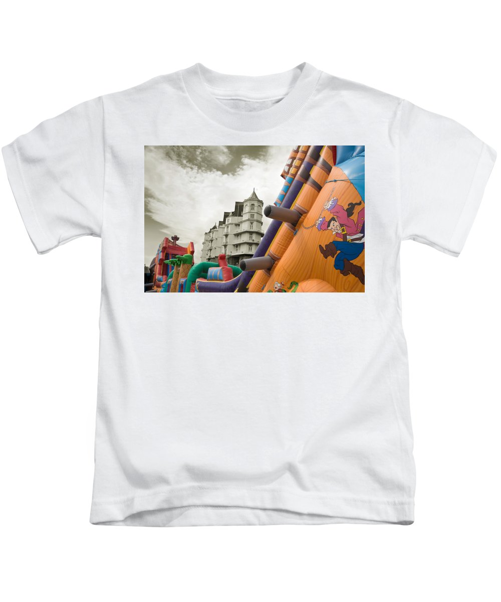 Childrens Kids T-Shirt featuring the photograph Childrens Play Areas Contrast With The Victorian Elegance Of The Grand Hotel In Llandudno Wales Uk by Mal Bray