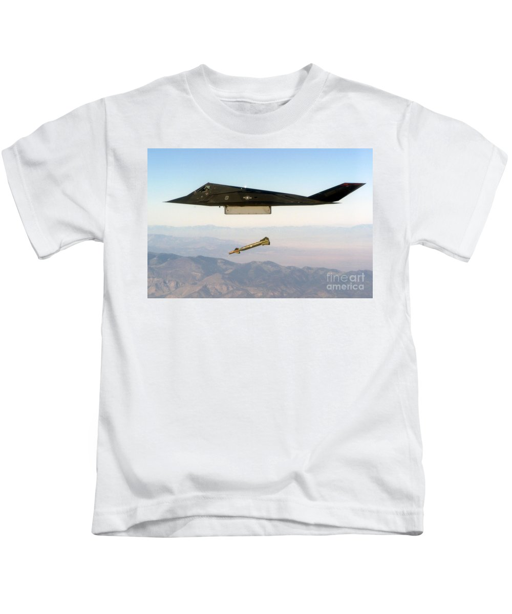 F 117 Nighthawk Engages Its Target And Drops A Gbu 28 Guided Bomb Kids T-Shirt featuring the photograph F 117 Nighthawk Engages Its Target And Drops A Gbu 28 Guided Bomb by R Muirhead Art