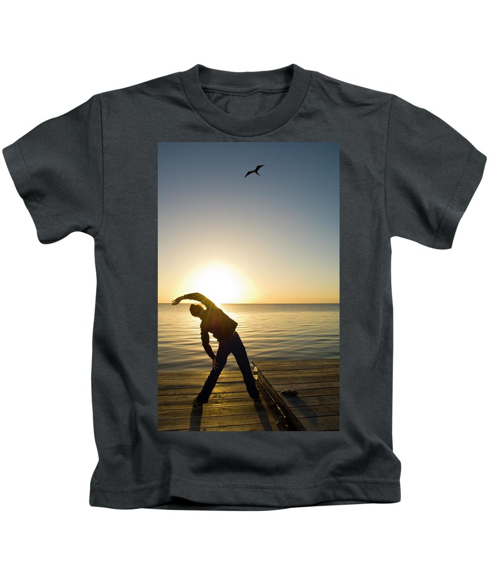 30s Kids T-Shirt featuring the photograph A Person Practices Yoga At The Waters by Kevin Steele