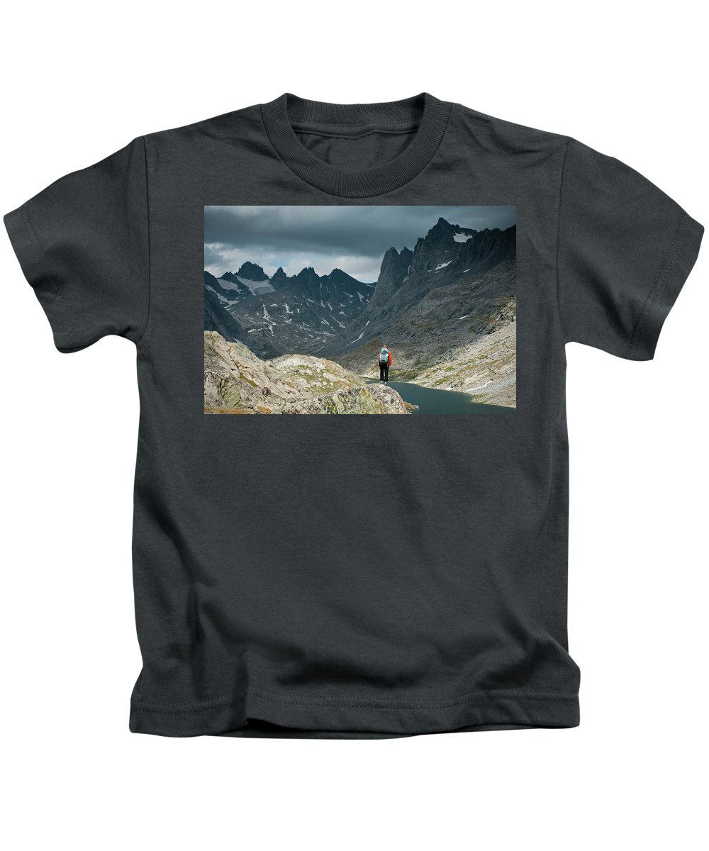 30-34 Years Kids T-Shirt featuring the photograph A Young Woman Takes In The View While by Jeff Diener