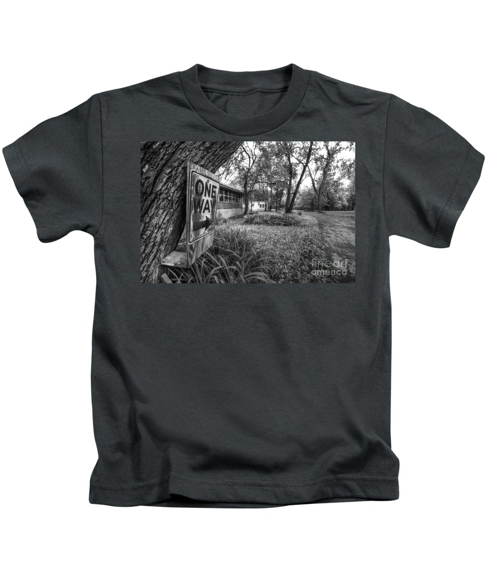 Sign; Signage; Tree; Posted; Post; Plants; Road; Street; Town; Neighborhood; Trees; Houses; Homes; Pavement; Grass; Yard; Curve; Bend; One Way; One; Arrow; Law; Black; White; Monochrome Kids T-Shirt featuring the photograph One Way by Margie Hurwich