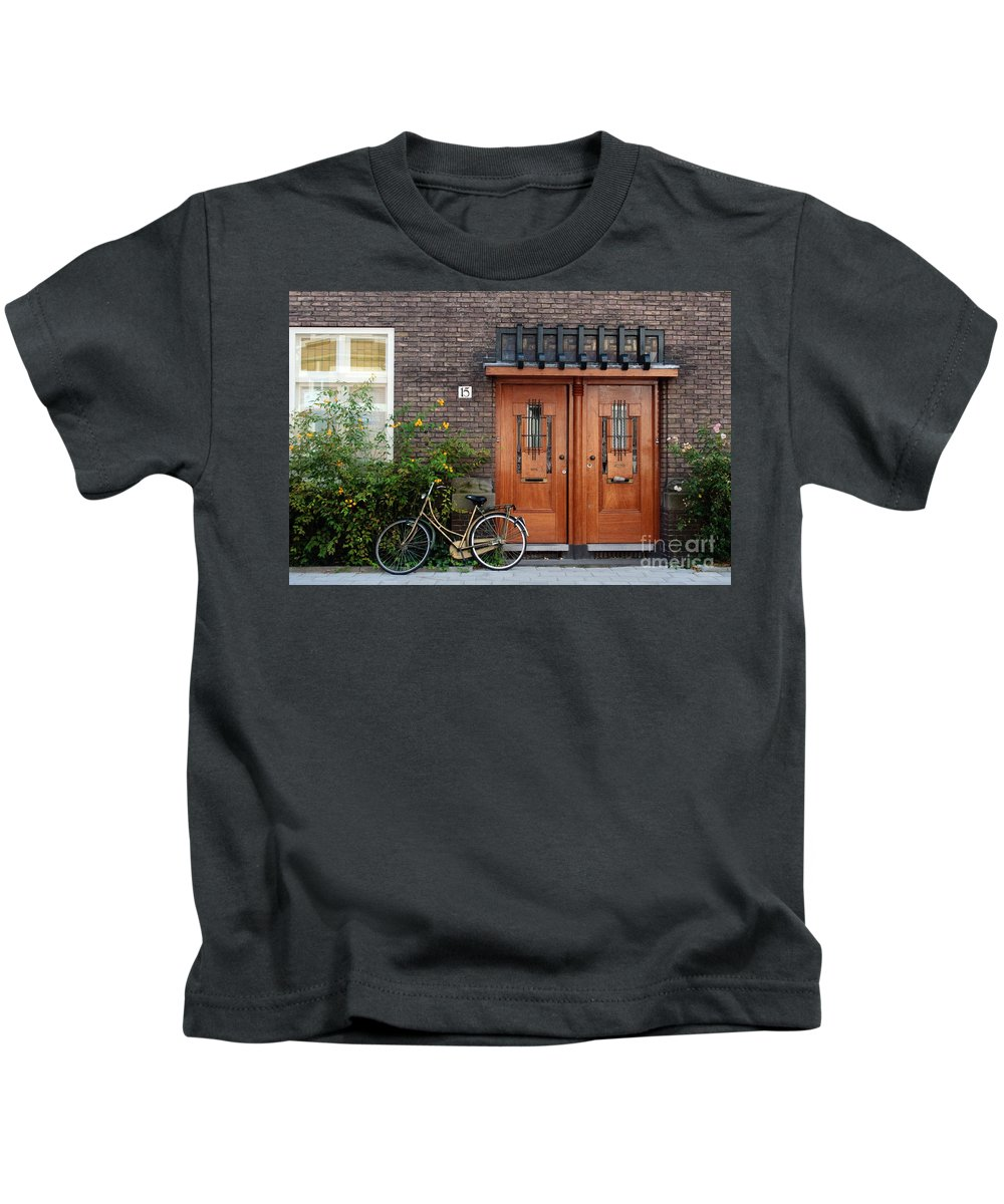 Bicycle Kids T-Shirt featuring the photograph Bicycle And Wooden Door by Thomas Marchessault