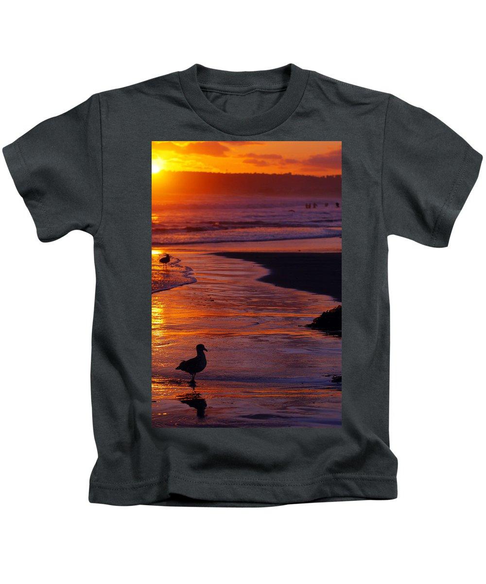 Beach Ocean Bird Sunset Orange Waves Kids T-Shirt featuring the photograph Bird At Sunset by Jill Reger