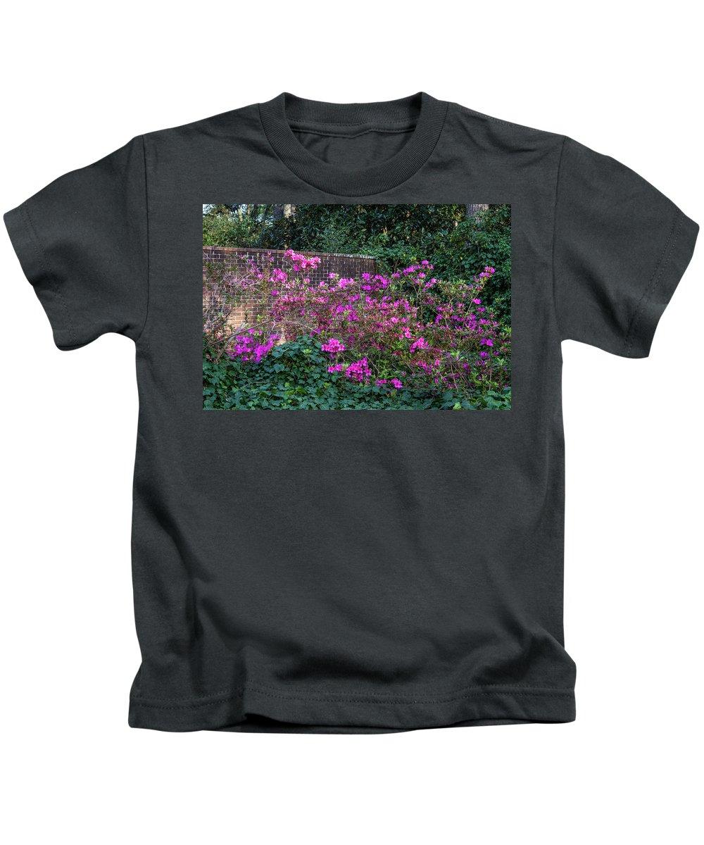 Hopelands Garden Kids T-Shirt featuring the photograph Brick Wall And Azalea by Menachem Ganon