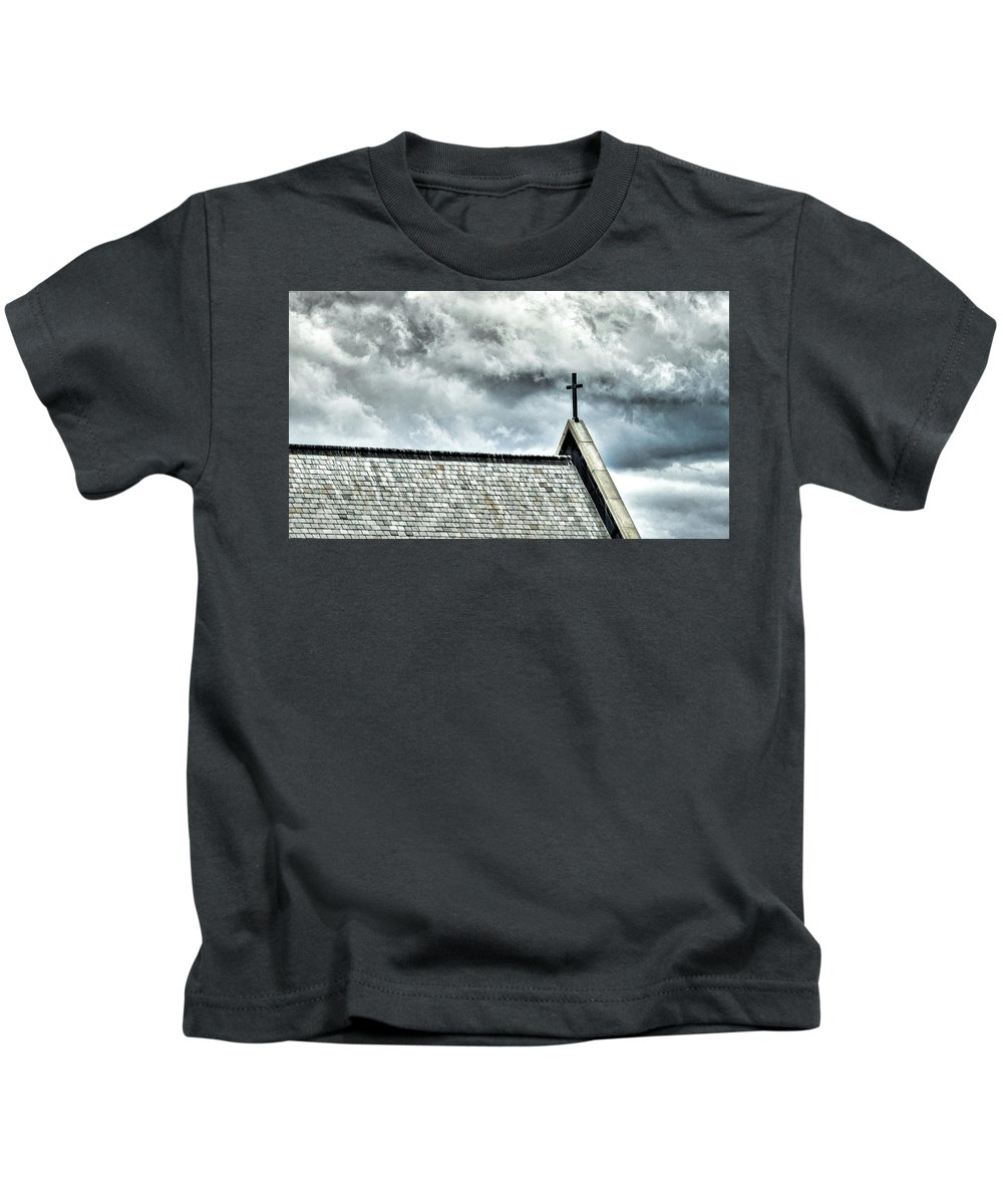 Cross Kids T-Shirt featuring the photograph Cross Against An Angry Sky by Bill Dussault