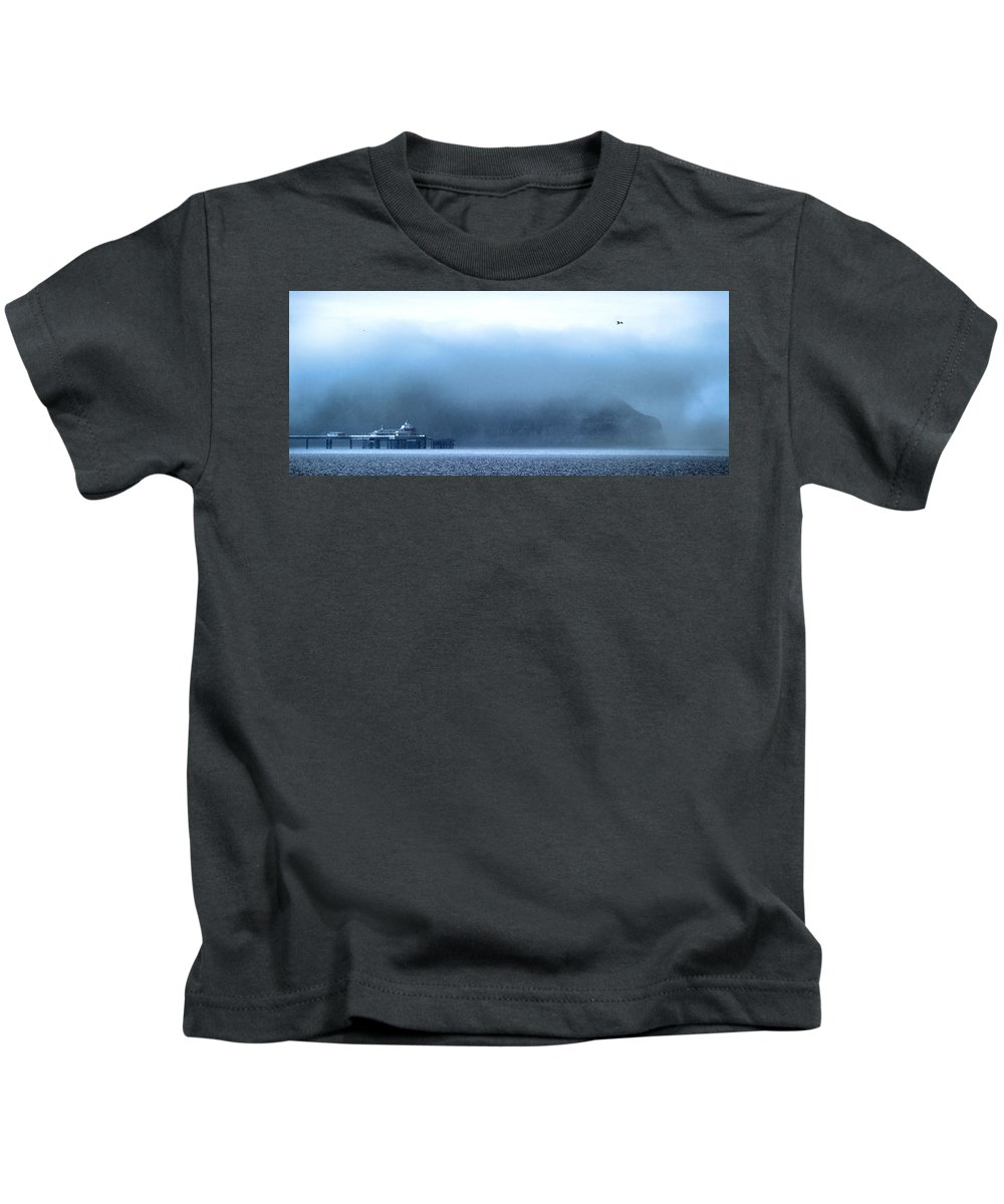Pier Kids T-Shirt featuring the photograph The Sea Mist Lifts To Reveal The Great Orme Behind Llandudno Pier by Mal Bray