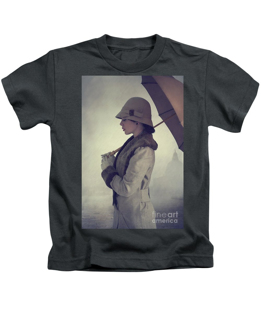 1940's Kids T-Shirt featuring the photograph Woman With Vintage Cloche Hat Overcoat And Umbrella In Rain by Lee Avison