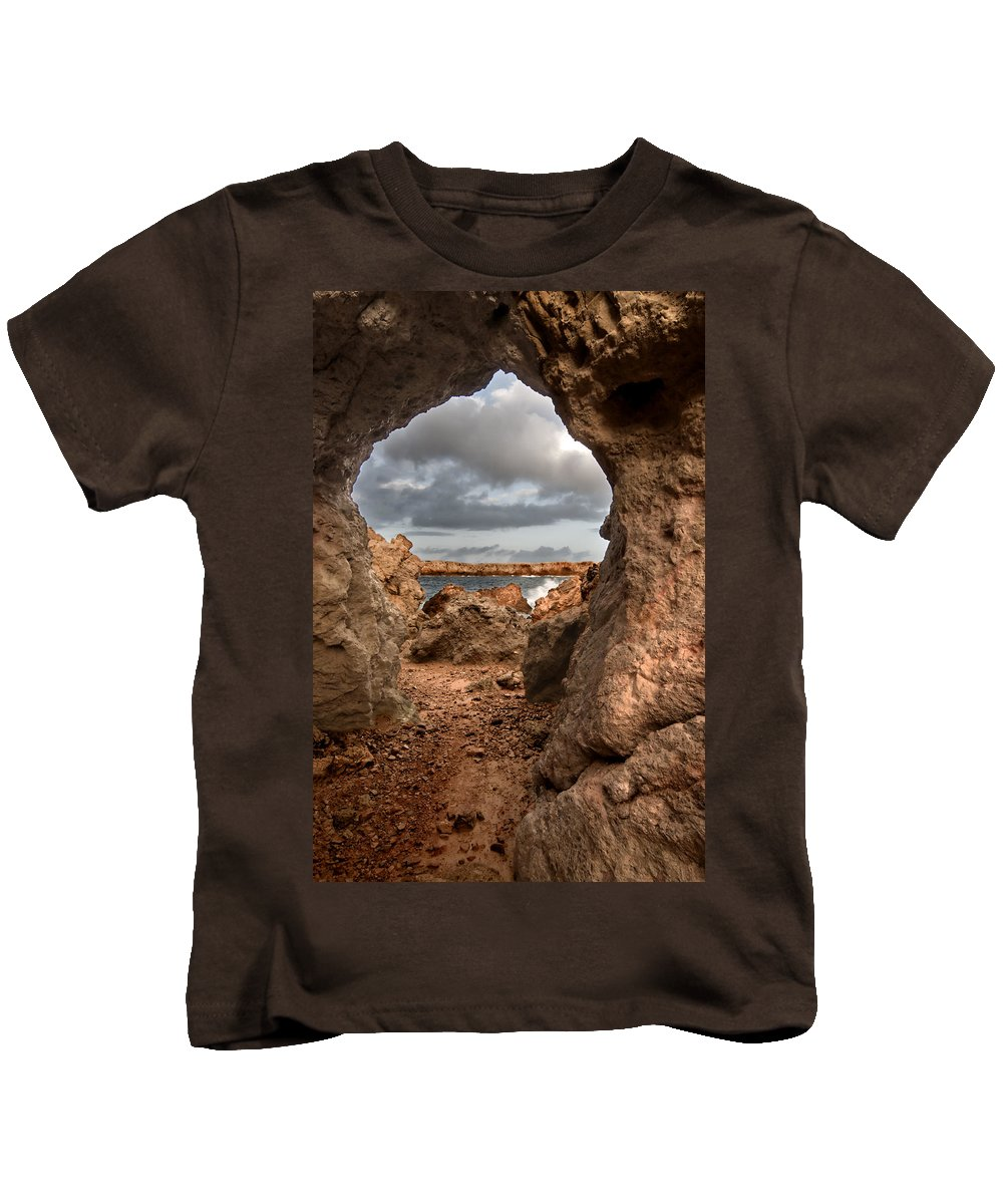 Alley Kids T-Shirt featuring the photograph A Natural Stone Arch In North Coast Of Minorca Appears Like A Pass To One Thousand And One Night by Pedro Cardona Llambias