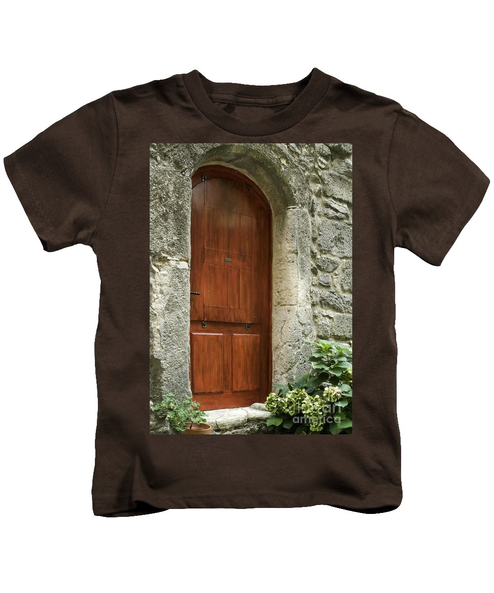 Saignon France Door Doors Stone Structure Structures Home Homes Building Buildings Provence Village Villages City Cities Cityscape Cityscapes Architecture Kids T-Shirt featuring the photograph What's Behind The Red Door by Bob Phillips