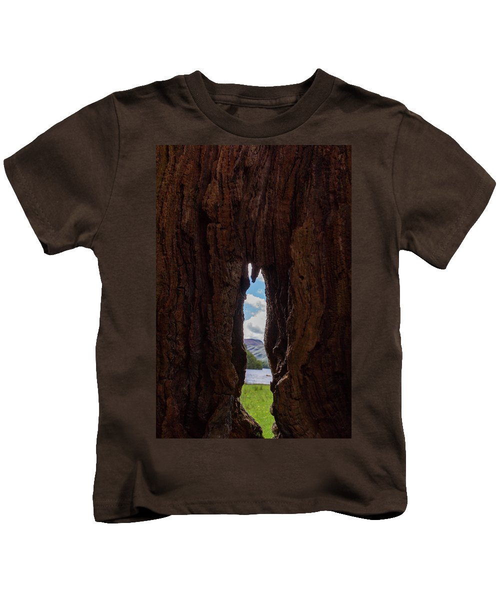 Cumbria Lake District Kids T-Shirt featuring the photograph Spot The Lake Shore View Through The Hollow Tree Trunk by Iordanis Pallikaras