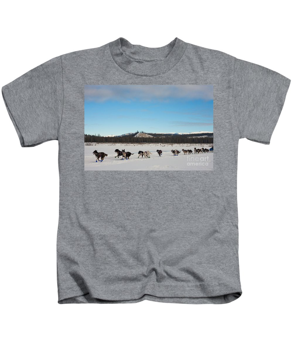 Action Kids T-Shirt featuring the photograph Team Of Sleigh Dogs Pulling by Stephan Pietzko
