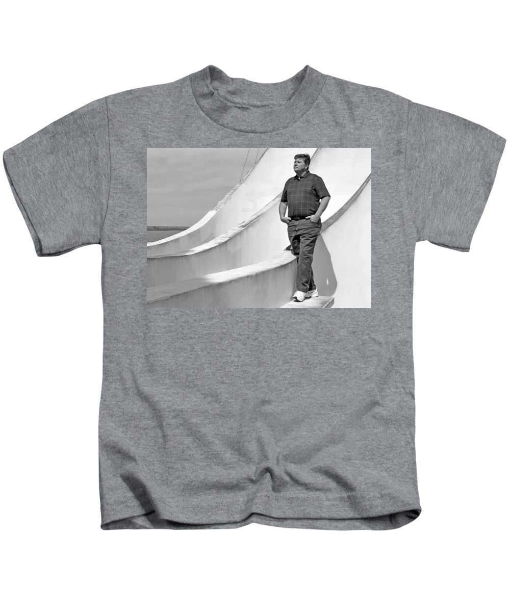 Black Kids T-Shirt featuring the photograph Man At Conrcete Structure by Bradley Bennett