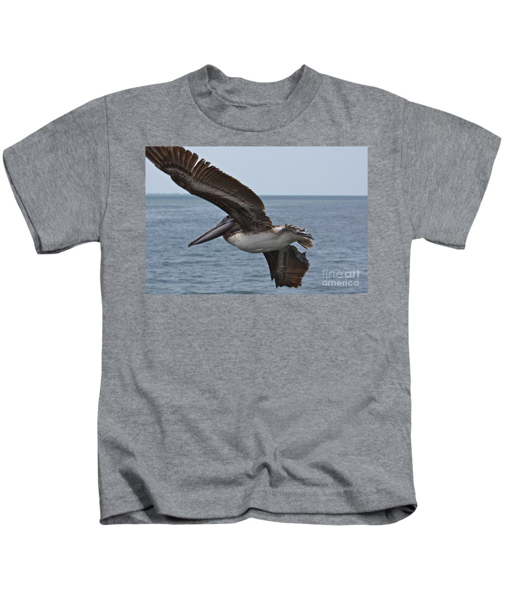 Pelican Kids T-Shirt featuring the photograph Pelican Fly By by Carol Groenen