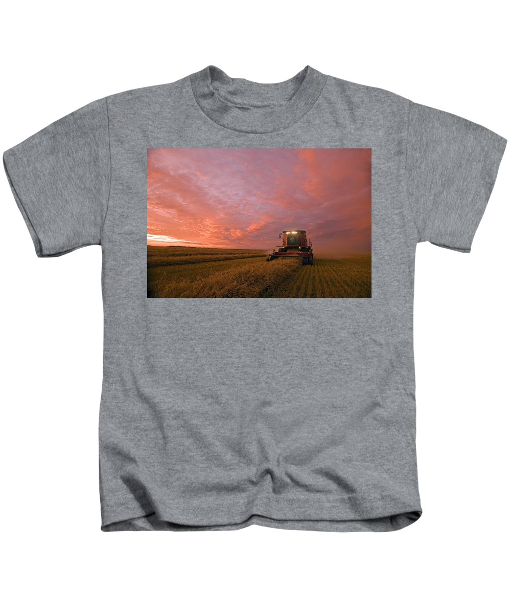 Canadian Kids T-Shirt featuring the photograph Farmer Harvesting Oat Crop by Dave Reede