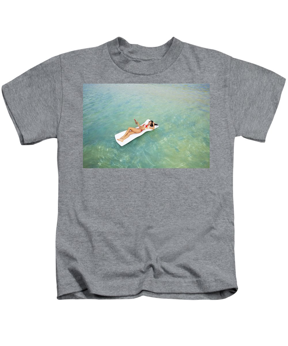 Alcohol Kids T-Shirt featuring the photograph Floating At Sea by Tomas del Amo - Printscapes