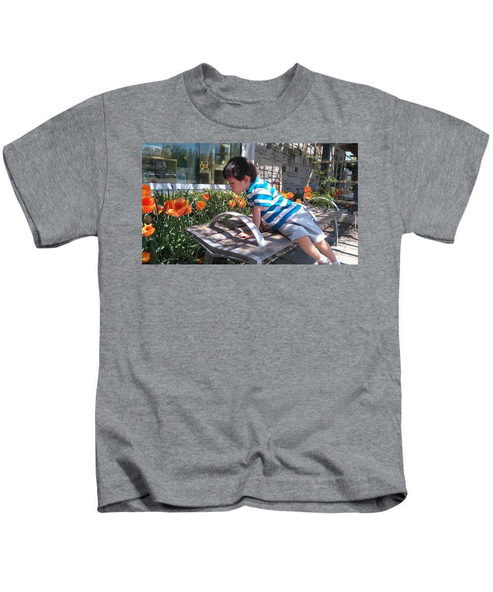 Little Boy Looking At Flower Bed Kids T-Shirt featuring the photograph Little Boy And Flowers by Connie Du