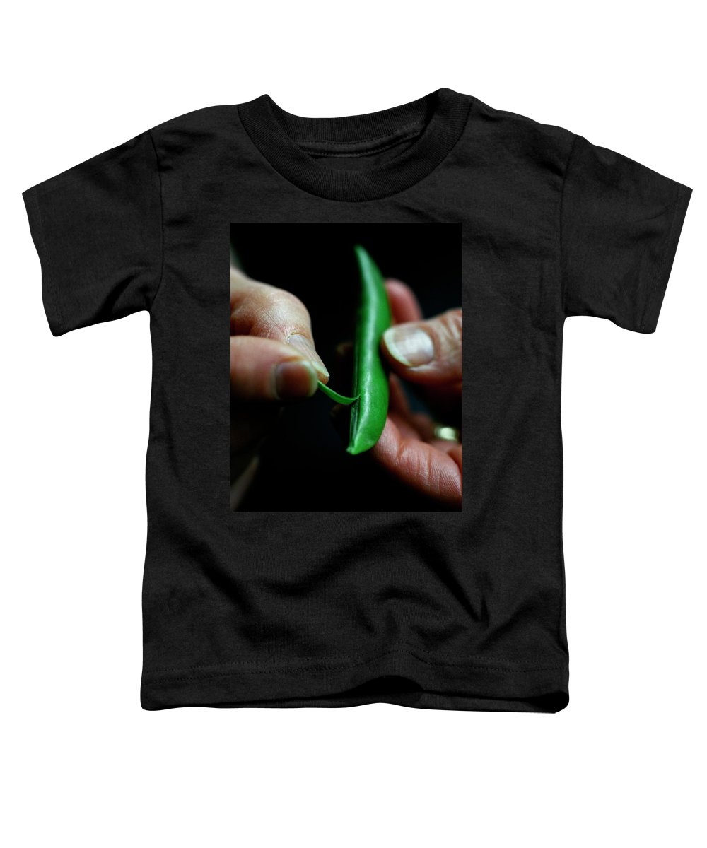 Fruits Toddler T-Shirt featuring the photograph A Person Peeling A Bean by Romulo Yanes