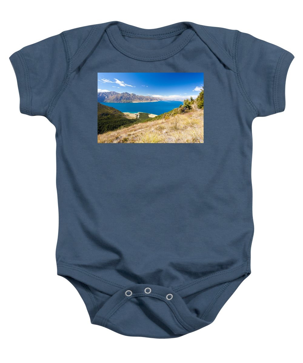 South Island Baby Onesie featuring the photograph Blue Surface Of Lake Hawea In Central Otago In New Zealand by Stephan Pietzko
