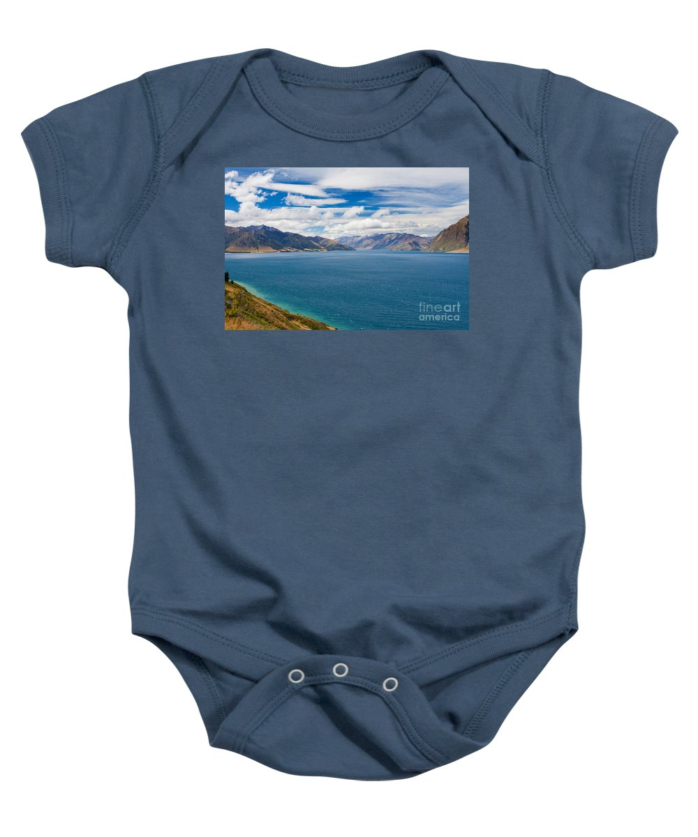 South Island Baby Onesie featuring the photograph Blue Surface Of Lake Hawea In Central Otago Of New Zealand by Stephan Pietzko